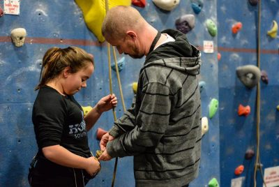Indoor Climbing - safety harness being fitted to girl